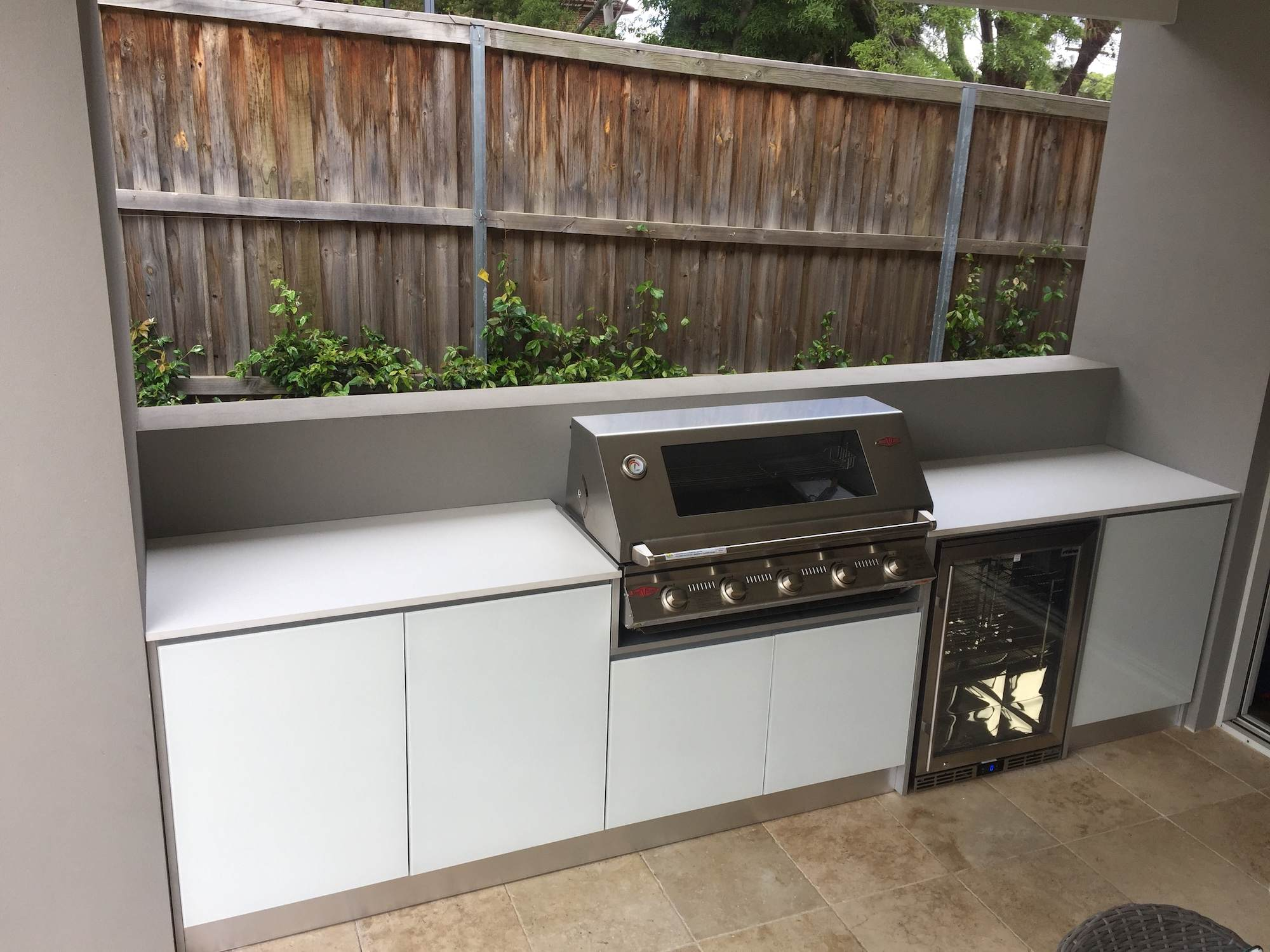 Full aluminium cabinets, with 5mm white tempered glass doors and 20mm Dekton bench tops in Nayla, complete with a Beefeater BBQ and Rhino Fridge.